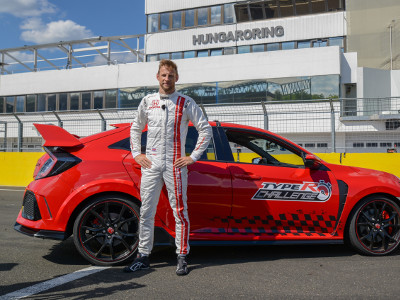A victorious Jenson Button stands next to his winning Type R